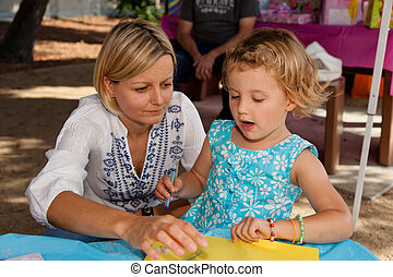 Arts and crafts - Mother helping her daughter during her art...