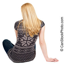 Back view of beautiful young woman sitting on the floor and...