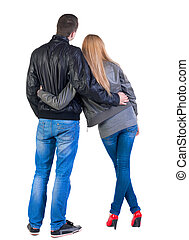 Back view of young couple man and woman hug and look into...