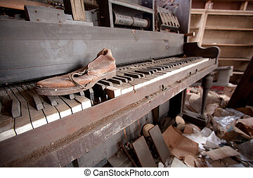 Old Piano And Shoe - An old leather shoe sitting on top of...