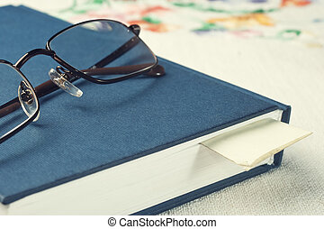 bookmark in a closed book - eyeglasses rest on a closed...