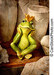 Frog prince sitting on a wooden shelf among vintage garden...