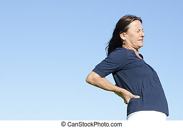 Woman suffering from back pain - A mature woman in pain,...