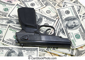Gun and dollars - automatic pistol lying on the U.S....