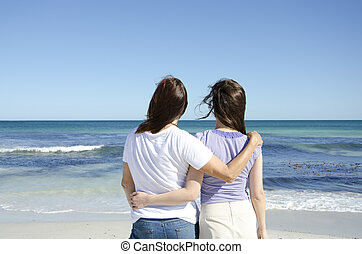 Lesbian couple at ocean - Two women, a happy lesbian couple...