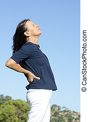 Mature woman and back pain - An attractive looking middle...