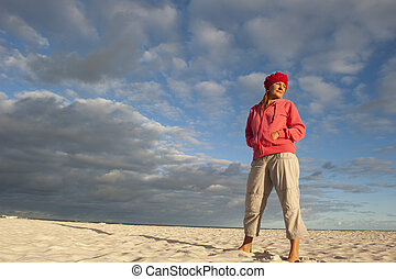 Pretty woman standing lonely at beach - Portrait of a...