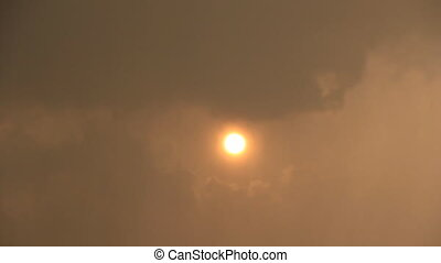 Sun disk through rain and dark cloud