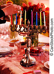Jewish Holidays Hanukkah - Hands of a woman is lighting a...