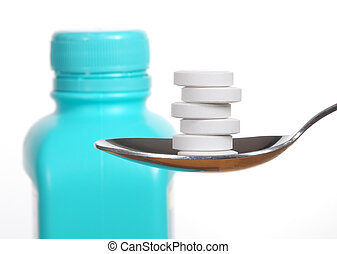 Antacid tablets on a spoon, a bottle of antacid blurred in...