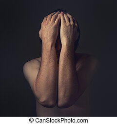 Depressive man - Sad man is covering his face with hands and...