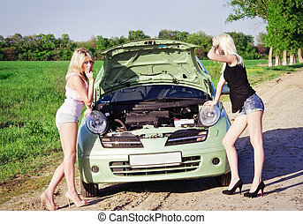 Two sexy blonde girls stand by the broken car and don't know...