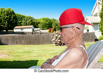 Red Hat - Older man with red hat turned backwards and...