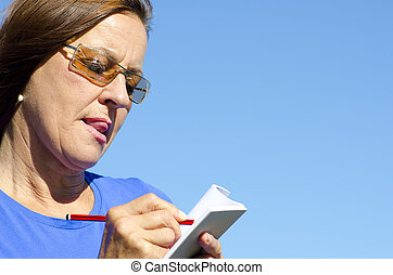 Woman taking notes - A mature woman is writing notes on a...