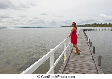 Woman on boardwalk over lake - A beautiful looking mature...