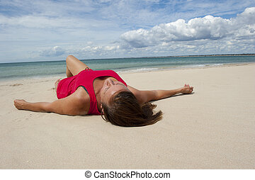 Sexy woman relaxed on remote beach - A beautiful looking...