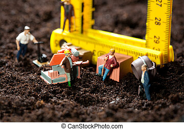 Miniature workmen building a house - Tiny miniature workmen...