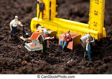 Miniature workmen building a house - Tiny miniature workmen...