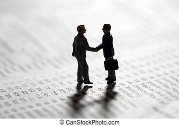 Sealing a business transaction with a handshake - Two tiny...