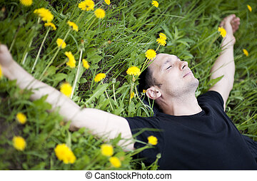 Young man relaxing on a grass with flowers