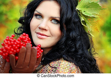 Portrait close up of woman with red berries, over green nature