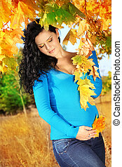 Pretty pregnant woman in autumn leaves outdoors, outdoors