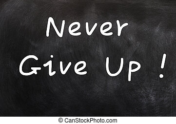 Never give up - words written in chalk on a blackboard