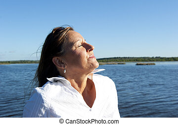 Portrait relaxed woman at lake - Portrait of confident and...