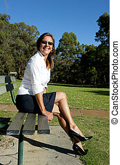 Business woman on park bench - Sexy high heeled mature...