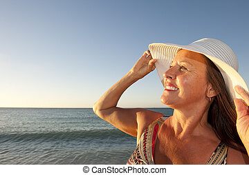 Portrait mature woman sunset ocean - Portrait of an...