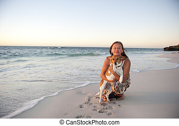 Woman and pet dog at ocean - Pretty looking mature woman is...