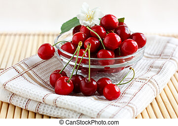 Fresh cherries in a glass cup with jasmine flower on a...