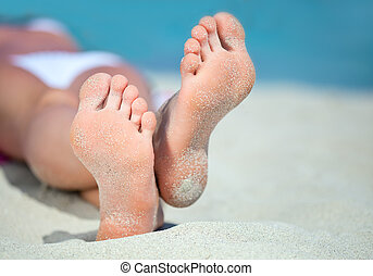 Feet on the beach - Womans feet on the white sand near the...