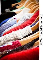 Rack of jumpers at market, close-up - Close-up on a rack of...