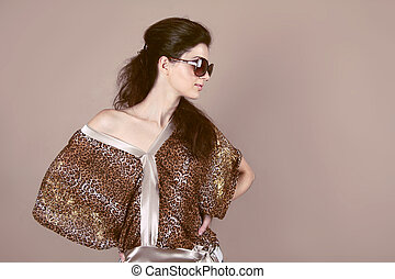 Fashion model woman with sun glasses posing in studio