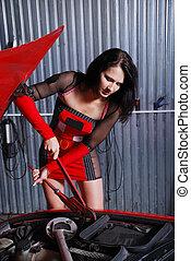 Pretty woman repairing the car.