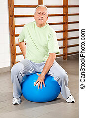 Senior Man Sitting On Fitness Ball - Full length of a senior...