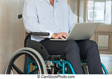 Man Sitting In Wheel Chair Using Laptop