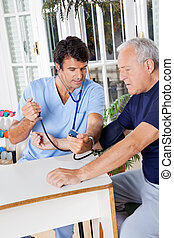 Male Nurse Checking Blood Pressure Of a Senior Patient -...