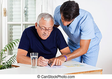 Male Nurse Helping Senior Man In Solving Puzzle - Young male...