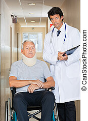Doctor Standing By Patient On Wheel Chair - Young doctor...