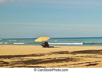 Blue skys and sandy beaches - An umbrella and beach chair on...