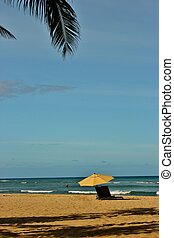 Blue skys and sandy beaches - An umbrella and beach chair on...
