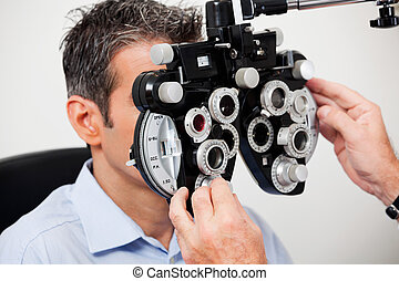 Eye Examination - Optometrist adjusting panels of phoropter...