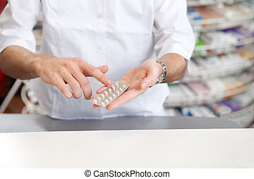 Male Pharmacist Giving Prescription Medicine In Pharmacy...