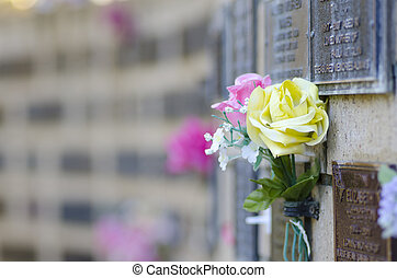 Flowers at grave in cemetery - Pink and yellow roses as...