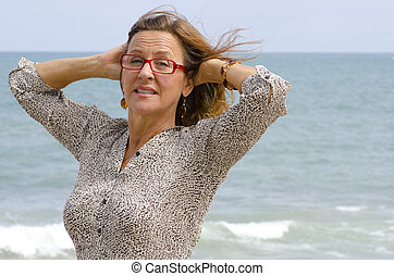 Mature woman at stormy ocean - An attractive looking middle...