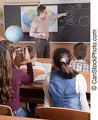 Male teacher in front of elementary age pupils - Male...