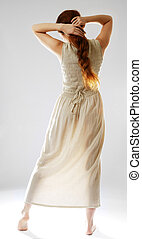 Barefoot girl in sundress - Young woman is standing back and...