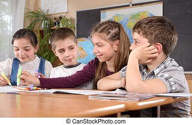 School routine - Four schoolchildren aged 11 at the desk in...